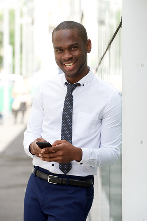 Portrait of handsome young african american businessman smiling with mobile phone in city
