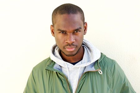Close up portrait of handsome young black man staring by wall