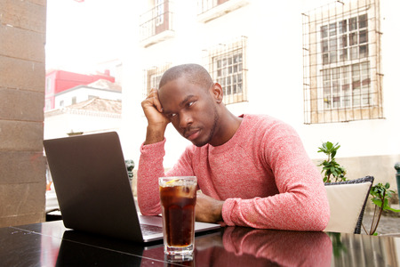 Portrait of young african american man sitting at cafe with laptop computer