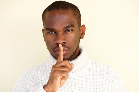 Close up portrait of african american man with finger over lips