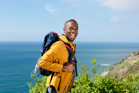 Portrait of happy african american man with walking backpack outdoors Stock Photo