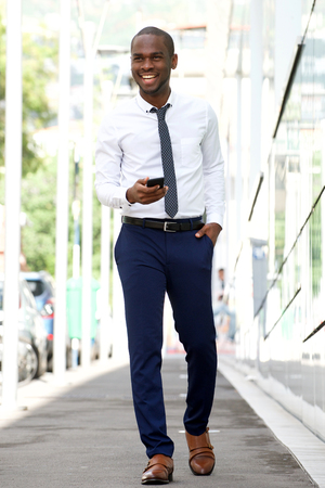 Full body portrait of smiling african american businessman walking on city street with cellphone Standard-Bild