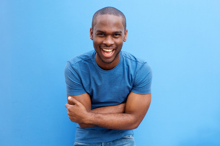 Portrait of handsome young african american man laughing with arms crossed