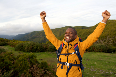 Portrait of happy african american backpacker standing outdoors with arms raised Imagens