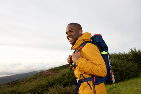 Side portrait of happy male backpacker walking in nature with bag Stock fotó - 118843449
