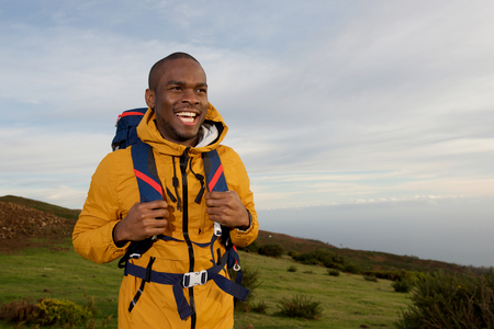 Portrait of smiling young black man with backpack walking in nature Stock fotó - 118843777