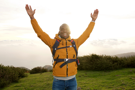Portrait of happy african american backpacker standing outdoors with hands raised Stock fotó - 118843782