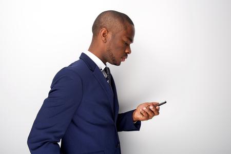 Zijportret van jonge zwarte zakenman die naar mobiele telefoon kijkt