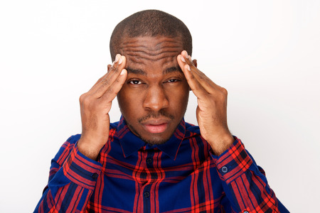 Close up portrait of young black man with headache and fingers pressing against head 版權商用圖片