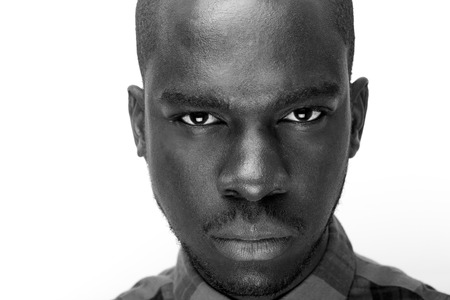 Close up black and white portrait of young black man staring