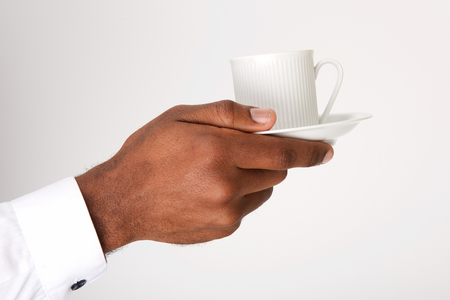 Close up african american male hand holding cup of coffee with saucer by white background