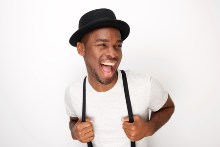 Portrait of handsome young black man laughing with hat and suspenders against white background 스톡 콘텐츠