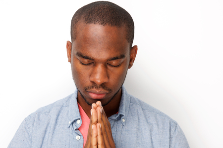 Close up portrait of young black man praying with hands clasp together Stock Photo