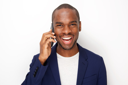 Close up portrait of cheerful young black man talking with cellphone by white background Stock Photo