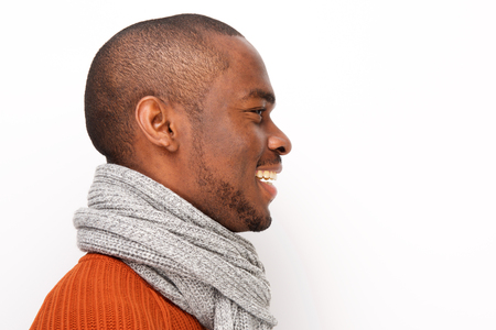Profile portrait of smiling black man with scarf against white background