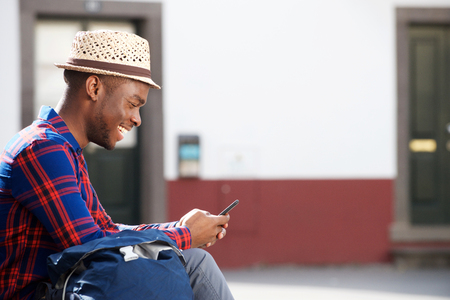 Side of happy african american man sitting outside and looking at mobile phone