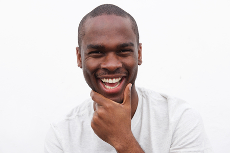 Close up portrait of handsome young black man smiling with hand to chin Foto de archivo