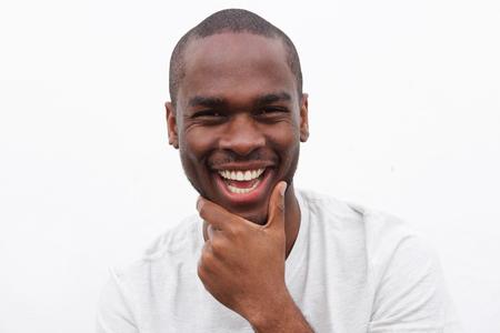 Nahaufnahme des Porträts eines gutaussehenden jungen schwarzen Mannes, der mit der Hand zum Kinn lächelt Standard-Bild