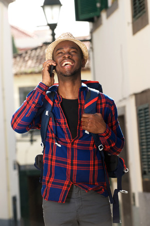 Portrait of african american travel man smiling with backpack and talking on cellphone