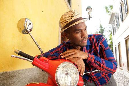 Portrait of handsome african american man leaning on scooter outdoors