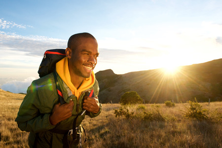 Portrait of young black man walking with backpack in mountains with sunrise in background