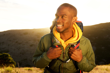 Close up portrait of handsome young african american man with backpack smiling with sunrise in background