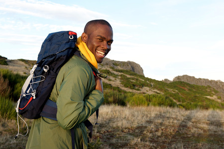 Side portrait of happy african american man hiking with backpack in the mountains