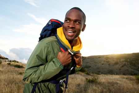 Side portrait of smiling african american man with backpack hiking in mountains