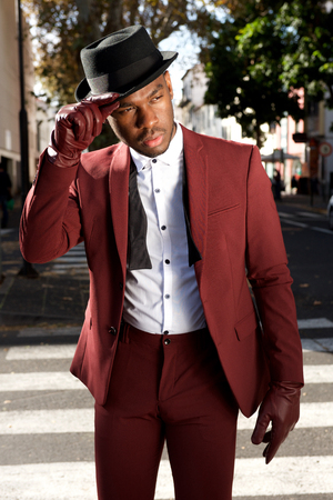 Portrait of cool african american male fashion model posing on city street with vintage suit and hat Stockfoto