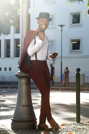 Full body portrait of cool african american fashion model with vintage suit posing with mobile phone in city