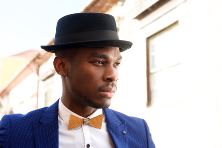 Close up portrait of handsome african american man with bowtie and hat