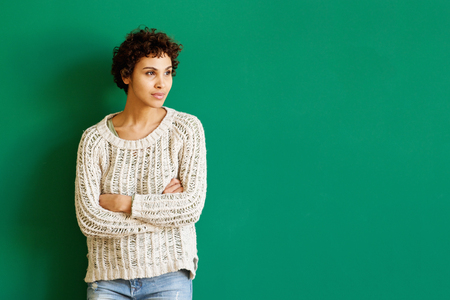 Portrait of young african american woman standing against green background with arms crossed