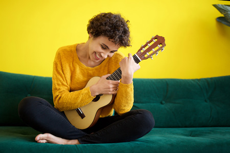 Portrait of happy young african american woman sitting on sofa with guitar instrument
