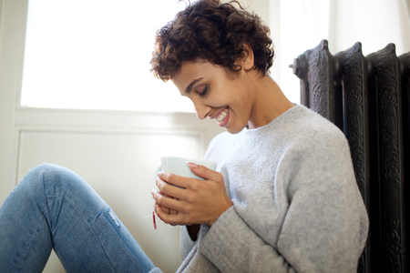 Portrait of relaxed young woman sitting on floor against radiator heater with cup of tea