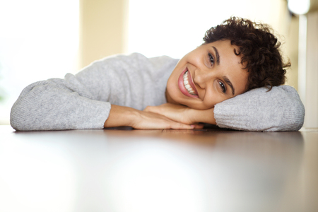 Close up portrait of beautiful young african american woman smiling with head relaxing on arms