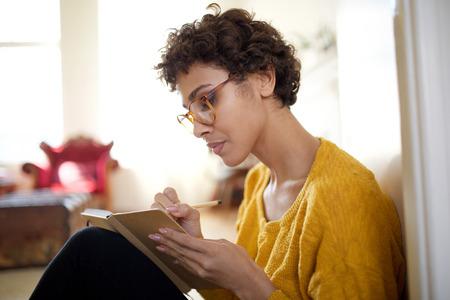 Nahaufnahme Porträt der jungen Afroamerikanerin mit Brille in Buch schreiben Standard-Bild