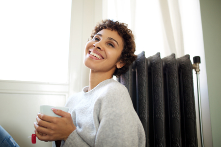 Portrait of young woman sitting on floor against radiator heater with cup of tea