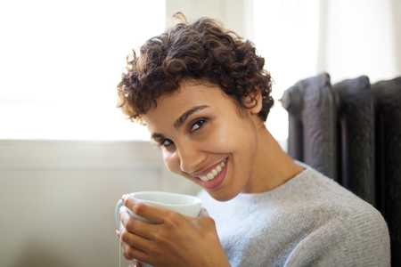 Close up portrait of young african american woman drinking hot tea from cup