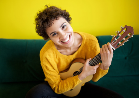 Portrait of happy young african american woman sitting with guitar instrument Reklamní fotografie