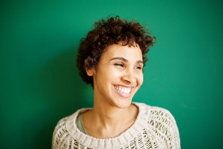 Close up portrait of happy young african american woman against green background