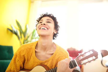 Close up portrait of happy young african american woman laughing with guitar Reklamní fotografie
