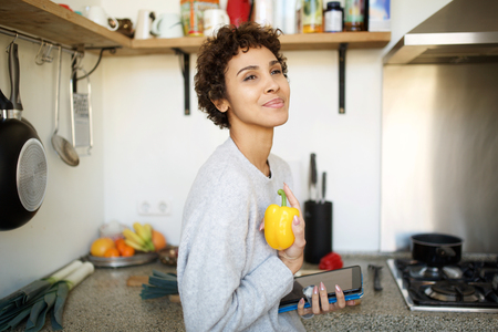 Side portrait of young woman in kitchen holding vegetable and digital tablet