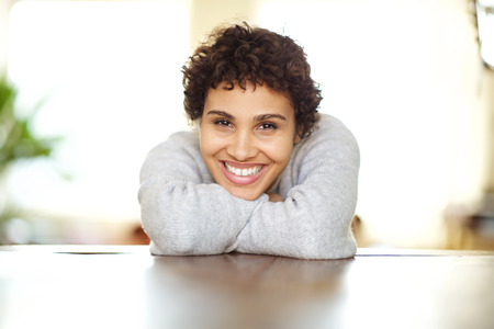Close up front portrait of happy young african american woman leaning on table Reklamní fotografie