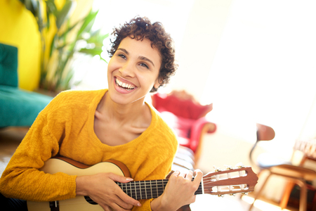 Portrait of young african american woman smiling with guitar at home