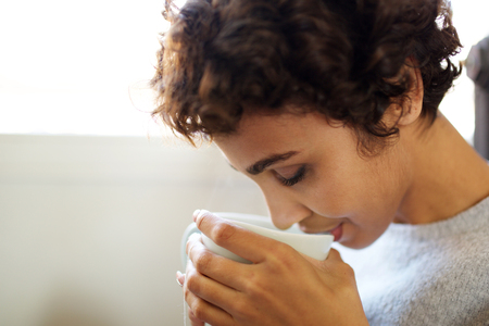 Close up portrait of young african american woman drinking tea from cup