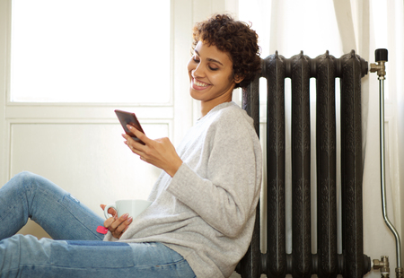 Portrait of young african american woman sitting on floor next to radiator and looking at mobile phone