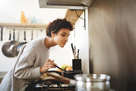 Portrait of young woman cooking and smelling food from pot