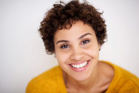 Close up portrait of smiling young mixed race woman smiling against white background
