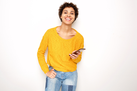 Portrait of cool young woman holding cellphone by white wall