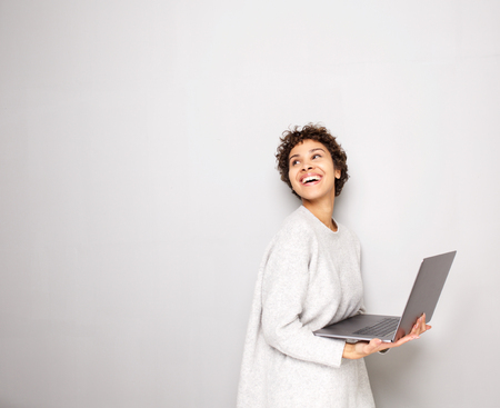 Portrait of happy young woman holding laptop computer by white wall